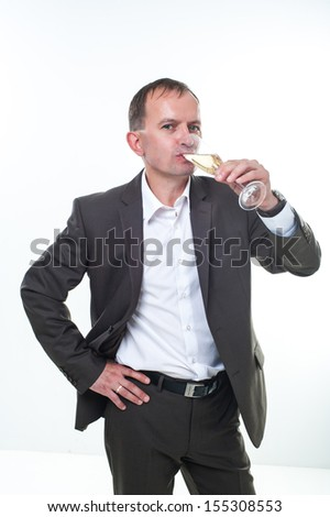 A mature male wearing a black tuxedo and bow tie raising a glass of champagne, isolated on a white background.