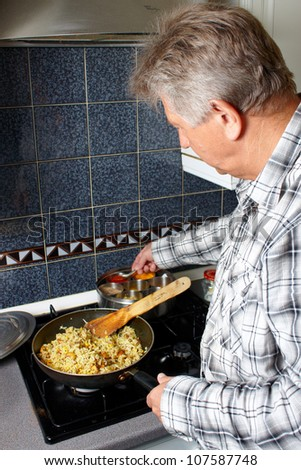 A mature man cooking a rice dish