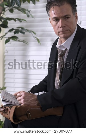 A mature man going through with a newspaper?s employment want ads. - stock photo