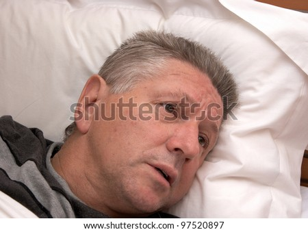 A mature man looking distressed while laying in bed