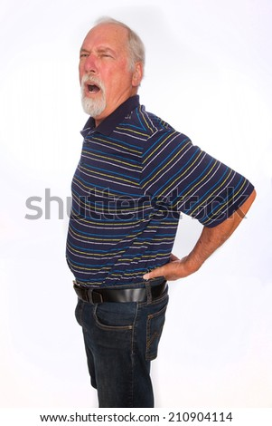 A mature man with an expression of pain as he holds his lower back - stock photo