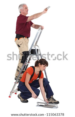 A mature manual worker and his young female apprentice.