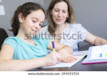 A Mature mother helping her child with homework at home. - stock photo