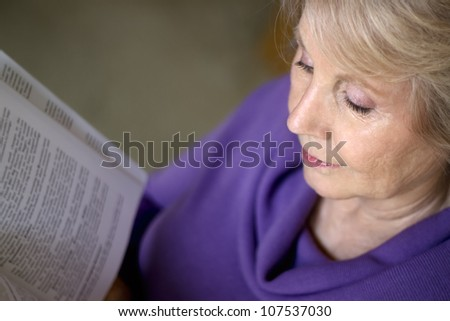 A mature older woman reading a book. - stock photo