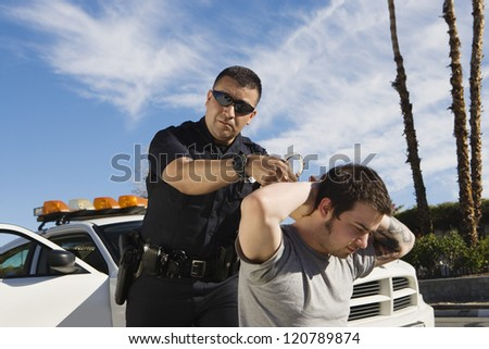 A mature police officer arresting young man - stock photo