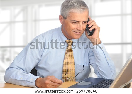A mature salesman talking on the telephone. The man is seated in a modern office with a laptop on his desk in front of a large bank of windows. - stock photo