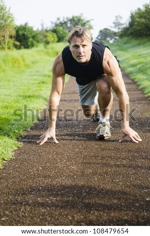 A mature sportsman in his forties crouches down in preparation for sprinting in a public park.