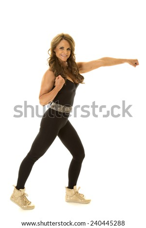 A mature woman doing a kickboxing punch. - stock photo