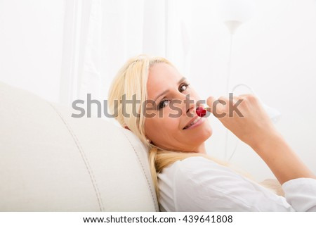 A mature woman enjoying cherries on the sofa. 
