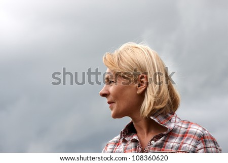 A mature woman head shot with stormy sky background