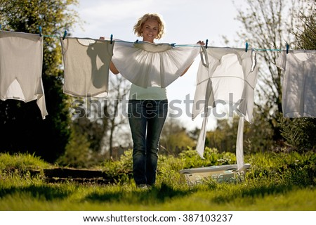 A mature woman pegging out washing on a washing line