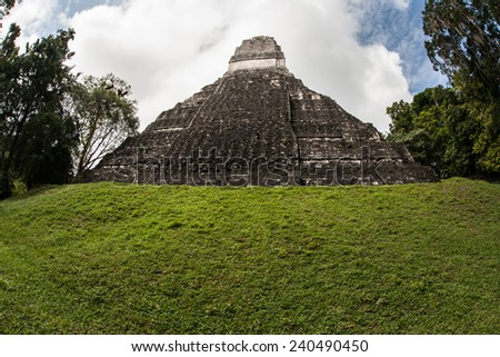 A Mayan temple rises out of the jungle in Tikal National Park, northern Guatemala. This archaeological site is one of the largest urban centers of pre-Columbian Maya civilization. - stock photo