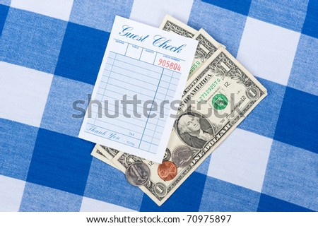 A meal check from a restaurant with change on a checkered table cloth - stock photo