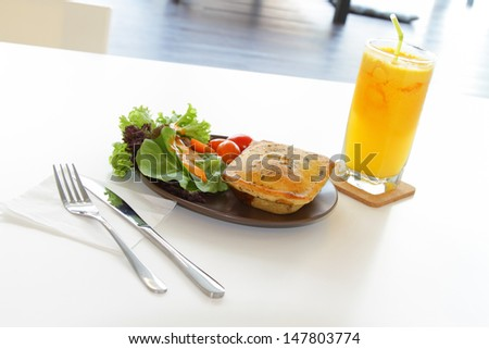 A meal of chicken pie with salad and a glass of orange juice - stock photo