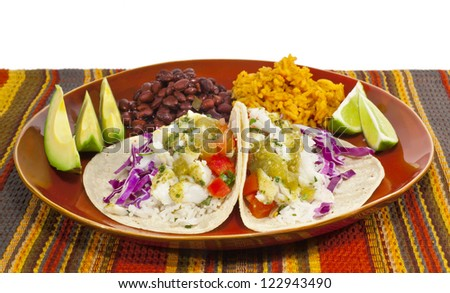 A meal of fish tacos with black beans and Mexican rice.