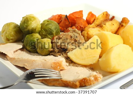 A meal of roast turkey with all the trimmings - brussels sprouts, roast sweet potatoes, roast parsnips stuffing and boiled potatoes - stock photo