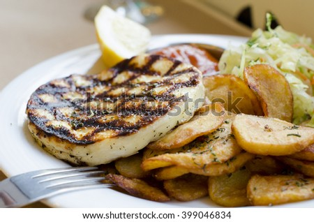 "A meal with Greek traditional white cheese ""Halumi"" or ""Talagani"" garnished with french fries served in a restaurant in Bulgaria - stock photo"