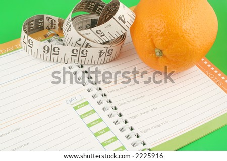 a measuring tape, diet and nutrition journal and an orange - stock photo