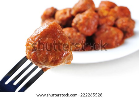 a meatball in a fork and a plate with a spanish meatballs stew on a white background - stock photo