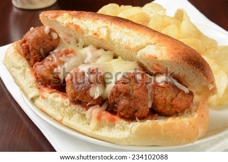 A meatball sandwich with mozzarella cheese and potato chips - stock photo