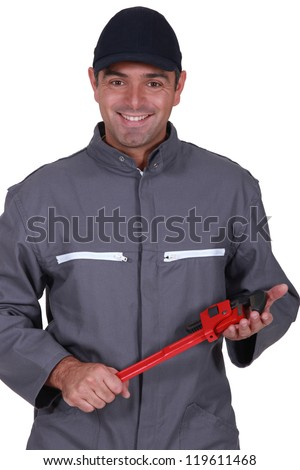A mechanic holding a wrench. - stock photo