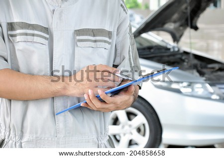 A mechanic holding clipboard in front of car engine - car checking & repairing concept - stock photo