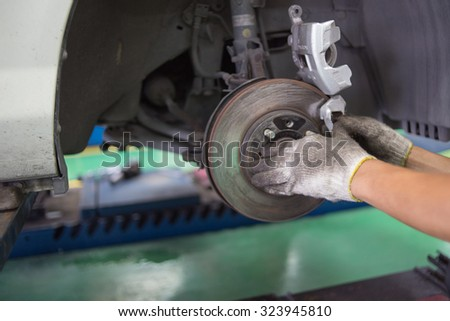 A mechanic is changing a wheel of a modern car - stock photo