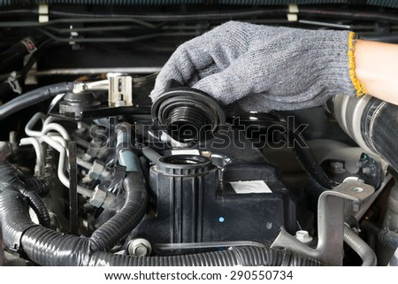 A mechanic is opening the oil cap from a car engine.
