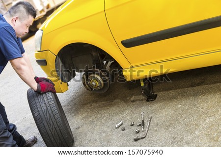 A mechanic looking troubled is preparing to change tire - stock photo