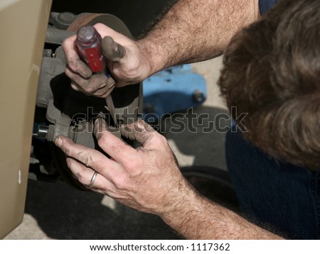 A mechanic opening the brake housing on a car to check the brake pads. - stock photo
