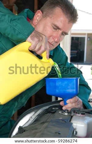 A mechanic pours radiator fluid into a car's radiator during normal maintenance. - stock photo