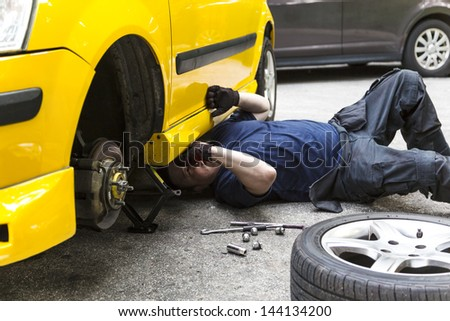 A mechanic underneath a car checking the car condition - stock photo
