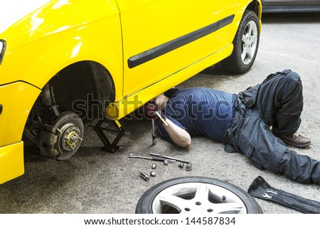 A mechanic underneath a yellow car doing maintain job.