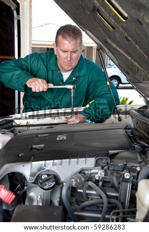 A mechanic works of a car during routine maintenance.