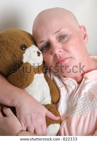 A medical patient hugging a teddy bear and looking afraid. - stock photo