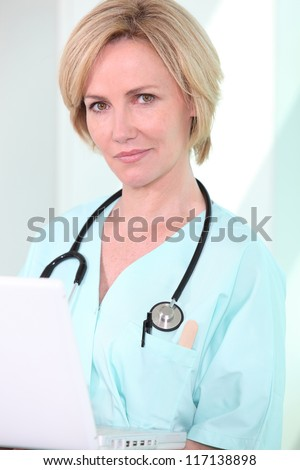 A medical professional looking at her laptop - stock photo