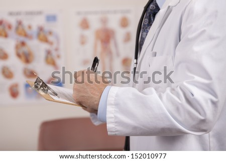 A medical professional writes information on a medical form while standing in a doctor's office.