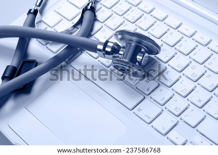 A medical stethoscope on a laptop, closeup - stock photo
