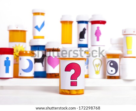 A medicine bottle with a 'question mark' label in front of other pill bottles background. - stock photo