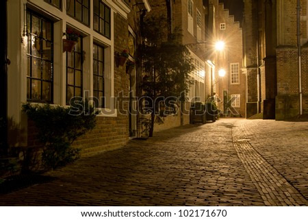 A medieval looking alley at night in the old city of Nijmegen in the Netherlands. Aged over 2000 years, Nijmegen is the oldest city in the country. - stock photo