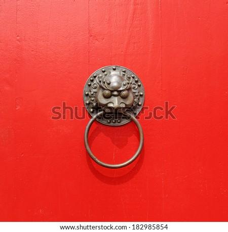 A medieval, oriental gargoyle head brass door knocker on a red wooden door panel.  - stock photo