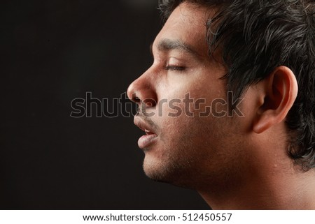 A meditating face with closed eyes  in a dark background