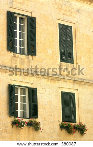 A mediterranean building facade with windows, some decorated with flowers, others have closed wood louvers. Photo shows detailed corrosion/weathering on  stone