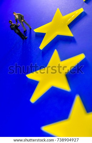 A meeting to discuss the Brexit issues.  Businessmen shown closeup on a EU flag.