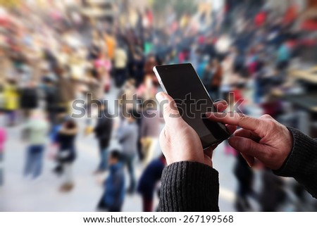 A men operating a smartphone in crowd background. - stock photo