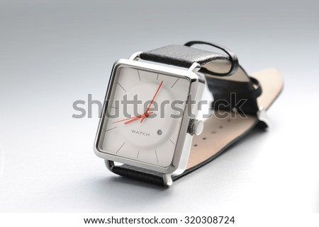 A men's wrist watch with simple and elegant white dial. - stock photo