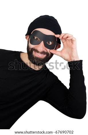 A men with beard dressed as a funny thief (black clothes, black woollen hat, masked eyes) smiling and popping out from one side as if looking for potential victims. - stock photo