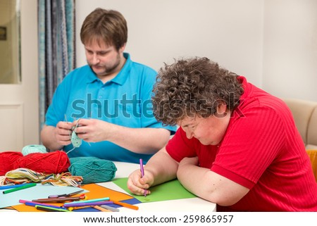 a mentally disabled woman and young man doing arts and crafts
