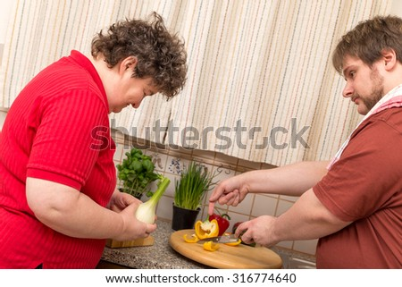 a mentally disabled woman learns cooking in the kitchen - stock photo