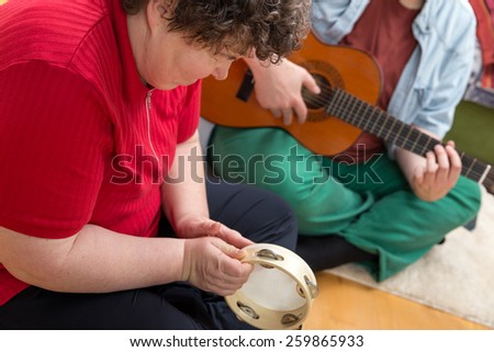 a mentally disabled woman playing a tambourine